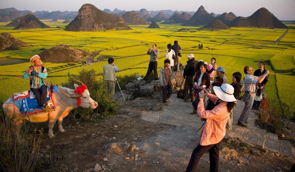 Foto che ritrae turisti che scattano foto a dei contadini asiatici