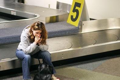 Foto di donn all'aeroporto che non trova il proprio bagaglio
