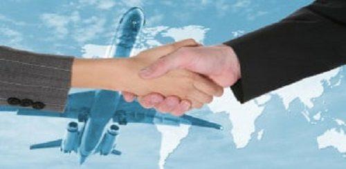 Una stratta di mano tra due persone e un aereo in volo nello sfondo