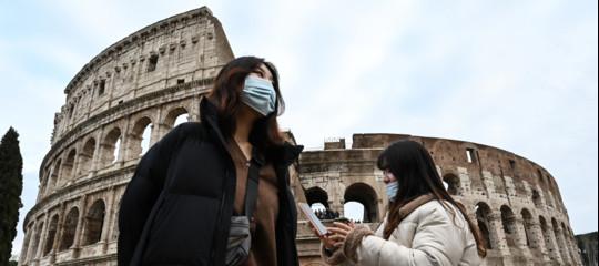 turisti cinese con mascherina e alle loro spalle il Colosseo